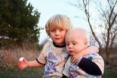 Hermanos que abrazan en la puesta del sol Imagen de archivo libre de regalías