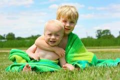 Hermanos que abrazan en toalla de playa Fotografía de archivo libre de regalías