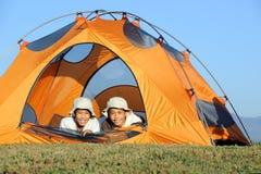 Hermanos que acampan hacia fuera en tienda Fotos de archivo