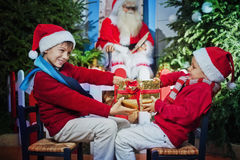 Hermanos que afirman para el regalo de la Navidad fotos de archivo libres de regalías