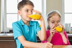 Hermanos que beben el zumo de naranja en cocina en casa Foto de archivo