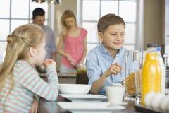 Hermanos que desayunan en la tabla con los padres que cocinan en fondo Fotos de archivo libres de regalías
