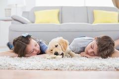 Hermanos que duermen con el perro en la manta Foto de archivo libre de regalías