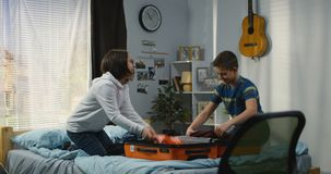 Hermanos que embalan una maleta en dormitorio almacen de metraje de vídeo