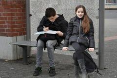 Hermanos que esperan en la parada de autobús escolar Fotografía de archivo libre de regalías
