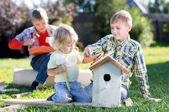 Hermanos que hacen la pajarera de madera por las manos El adolescente del niño enseña a su hermano menor Fotos de archivo libres de regalías