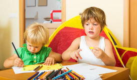 Hermanos que juegan con los lápices Fotos de archivo libres de regalías