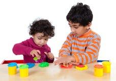 Hermanos que juegan con pasta del juego Imágenes de archivo libres de regalías