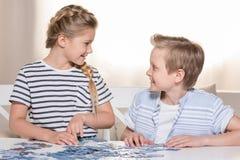 Hermanos que juegan con rompecabezas en la tabla en casa junto Fotos de archivo libres de regalías