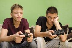 Hermanos que juegan el aburrimiento de los videojuegos Imagen de archivo libre de regalías