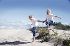 Hermanos que juegan en la playa Imagen de archivo libre de regalías