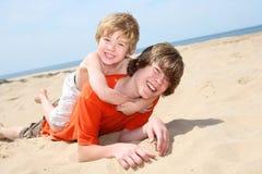 Hermanos que juegan en la playa Foto de archivo
