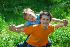 Hermanos que juegan en prado Fotos de archivo
