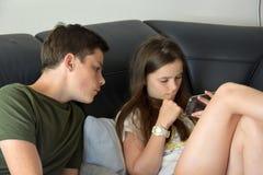 Hermanos que juegan en su smartphone Fotos de archivo libres de regalías