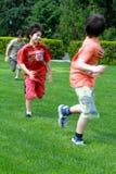 Hermanos que juegan la etiqueta en el parque Fotos de archivo