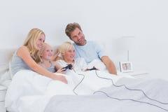 Hermanos que juegan a los videojuegos con la observación de los padres Imagen de archivo libre de regalías