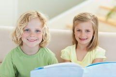 Hermanos que leen el folleto en el sofá Fotografía de archivo libre de regalías