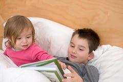 Hermanos que leen junto Imagenes de archivo