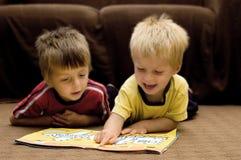 Hermanos que leen junto Imagen de archivo libre de regalías