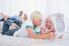 Hermanos que mienten en la alfombra usando la tableta digital Foto de archivo libre de regalías