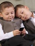 Hermanos que miran al teléfono Imagen de archivo libre de regalías
