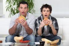 Hermanos que comen las hamburguesas Fotografía de archivo