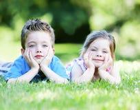 Hermanos que ponen en la hierba Imagenes de archivo