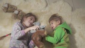 Hermanos que ruedan en la alfombra mullida Brother y la hermana se divierten Fin de semana feliz de los niños Cámara lenta almacen de metraje de vídeo
