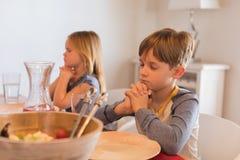 Hermanos que ruegan antes de tener comida en la mesa de comedor imagen de archivo libre de regalías