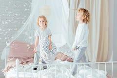 Hermanos que se colocan en cama Imagen de archivo