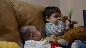 Hermanos que se sientan en el sofá - 3 meses del bebé y su más viejo hermano dos años almacen de metraje de vídeo