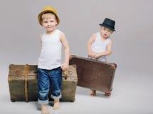 Hermanos que sostienen sus equipajes pesados Imágenes de archivo libres de regalías