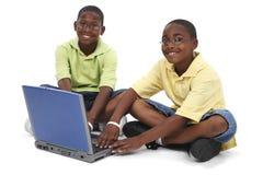 Hermanos que trabajan en el ordenador portátil que se sienta en suelo Imagenes de archivo