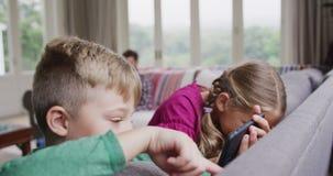 Hermanos que usan el teléfono móvil en el sofá en un hogar cómodo 4k almacen de metraje de vídeo