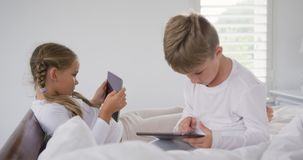 Hermanos que usan la tableta digital en el dormitorio en casa 4k almacen de metraje de vídeo