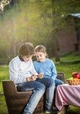 Hermanos que usan Smartphone en el sitio para acampar Imagen de archivo libre de regalías