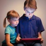 Hermanos que usan una tableta Imagen de archivo libre de regalías