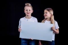 Hermanos sonrientes con la tarjeta en blanco imagen de archivo libre de regalías