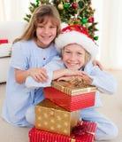 Hermanos sonrientes que sostienen los regalos de la Navidad Imagen de archivo libre de regalías