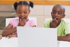 Hermanos sorprendidos que miran el ordenador portátil Fotografía de archivo libre de regalías