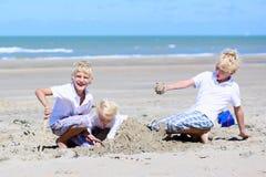 Hermanos y hermana que juegan en la playa Fotos de archivo