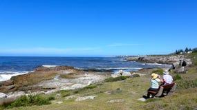 Hermanus, Südafrika Ein älteres Paar sitzt auf einer der vielen Bänke entlang Cliff Path und genießt die Ansicht Lizenzfreie Stockbilder