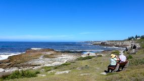 Hermanus, South Africa. An elderly couple sits on one of the many benches along the Cliff Path and enjoys the view Royalty Free Stock Images