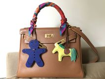 Hermes kelly bag size 28 epsom leather in gold color with silk twilly scarf petit h and rodeo bag charm. The classic Hermes kelly bag size 28 epsom leather in Royalty Free Stock Photos