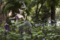 Hermes scolpisce in giardino porpora Fotografie Stock