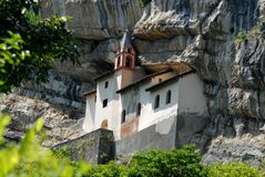 The Hermitage in the rock in Rovereto (Italy). Photo made hermitage of San Colombano near Rovereto in the province of Trento (Italy). The picture shows the old Stock Photo