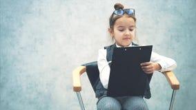 Hermosa joven empresaria con gafas. Sentado en un fondo gris con una carpeta en sus manos. Leer cuidadosamente almacen de video