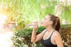 Hermosa, la muchacha del deporte de la aptitud con la cola de caballo bebe el agua en imagen de archivo