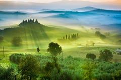 Hermosa vista de campos y de prados verdes en la puesta del sol en Toscana Imagen de archivo libre de regalías