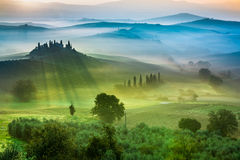 Hermosa vista de campos y de prados verdes en la puesta del sol en Toscana imagen de archivo